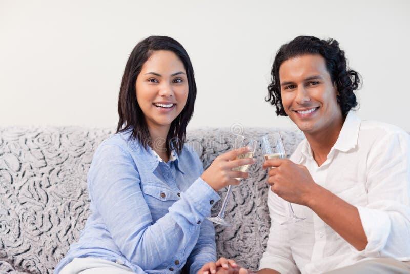 Couples ayant le vin mousseux sur le sofa image stock