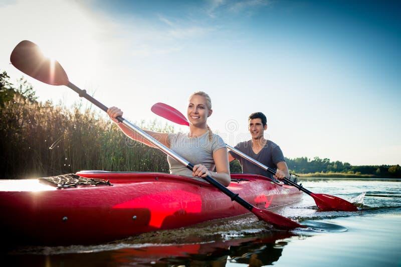 Couples barbotant dans le kayak photographie stock