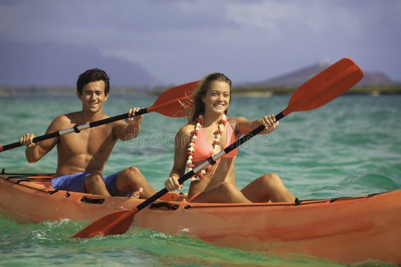 Couples barbotant leur kayak images libres de droits