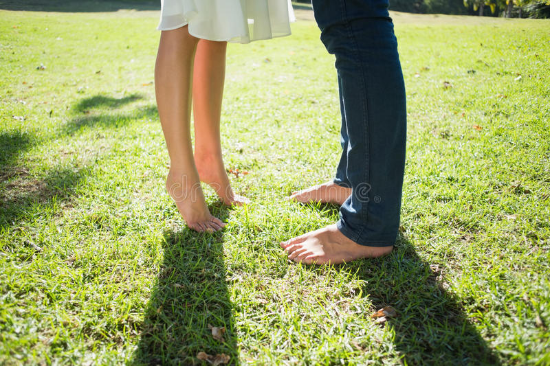 Couples bare feet standing on grass royalty free stock photography
