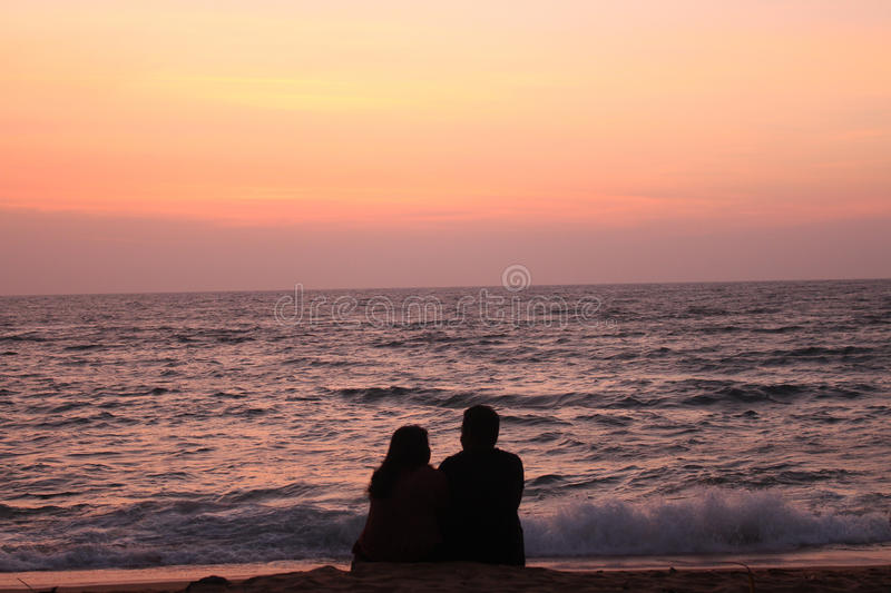 Couples in beach. In Dramatic red sunset over water royalty free stock photos