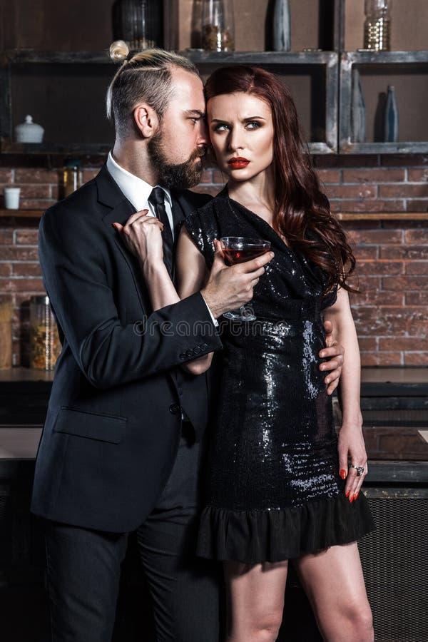 Couples c?l?bres habill?s par bien dans l'int?rieur de grenier Homme dans le style classique et lien, femme dans la robe noire Co photo libre de droits