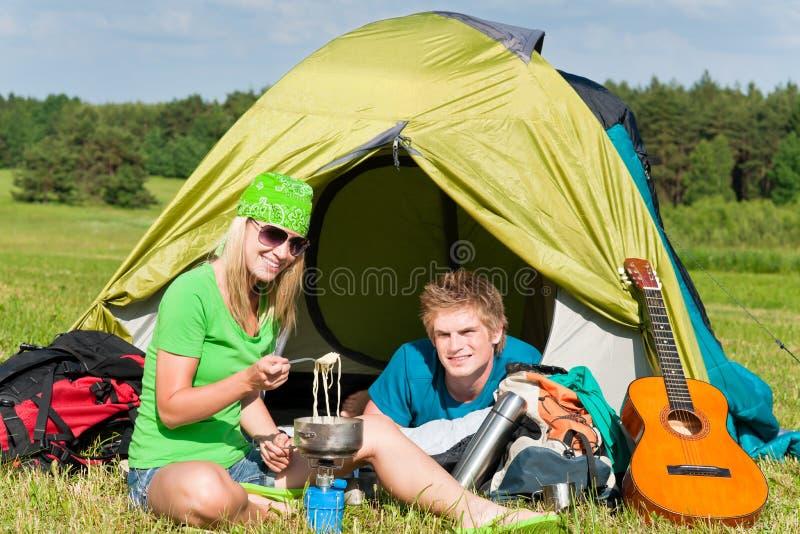Couples campants de jeunes faisant cuire le repas en dehors de la tente images libres de droits