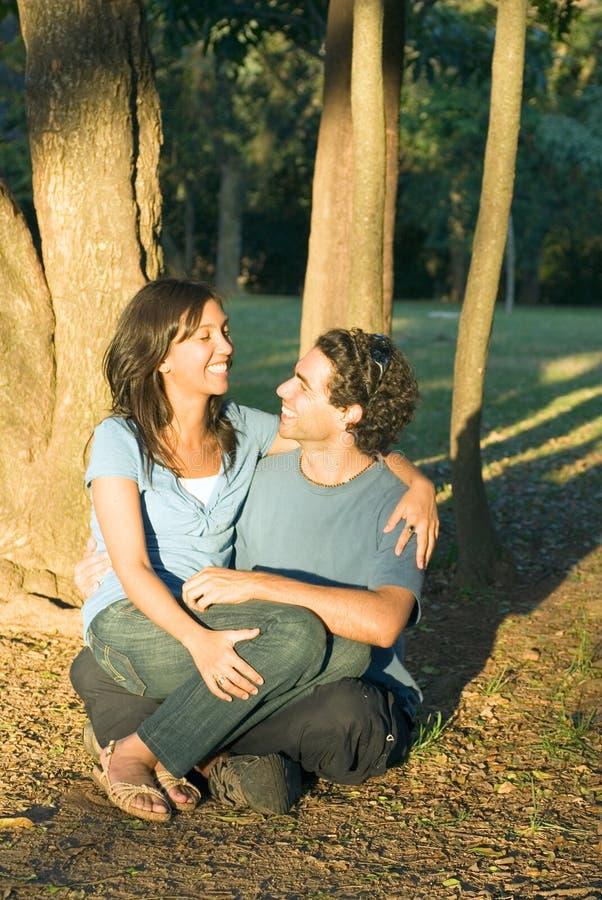 Couples caressant sous les arbres - verticale images stock