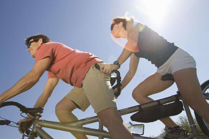 Couples caucasiens montant la bicyclette tandem photographie stock