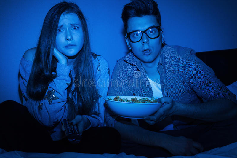 Couples caucasiens observant le film effrayant photos libres de droits