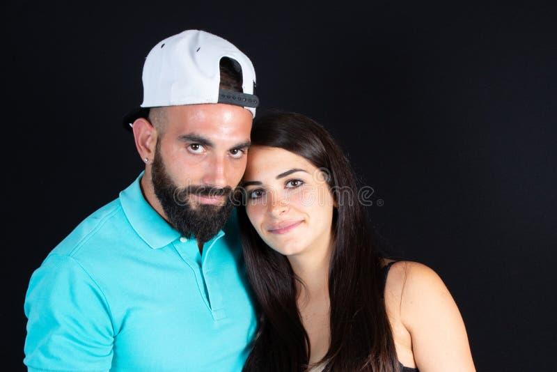 Couples chez homme barbu de femme de beauté d'étreinte d'amour le jeune et bel sur le fond noir photos stock