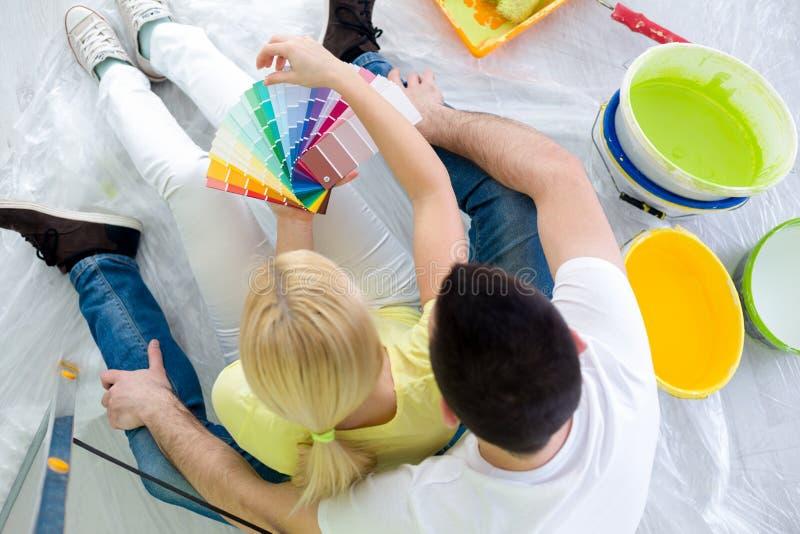 Couples choisissant des couleurs pour peindre la nouvelle maison photos stock