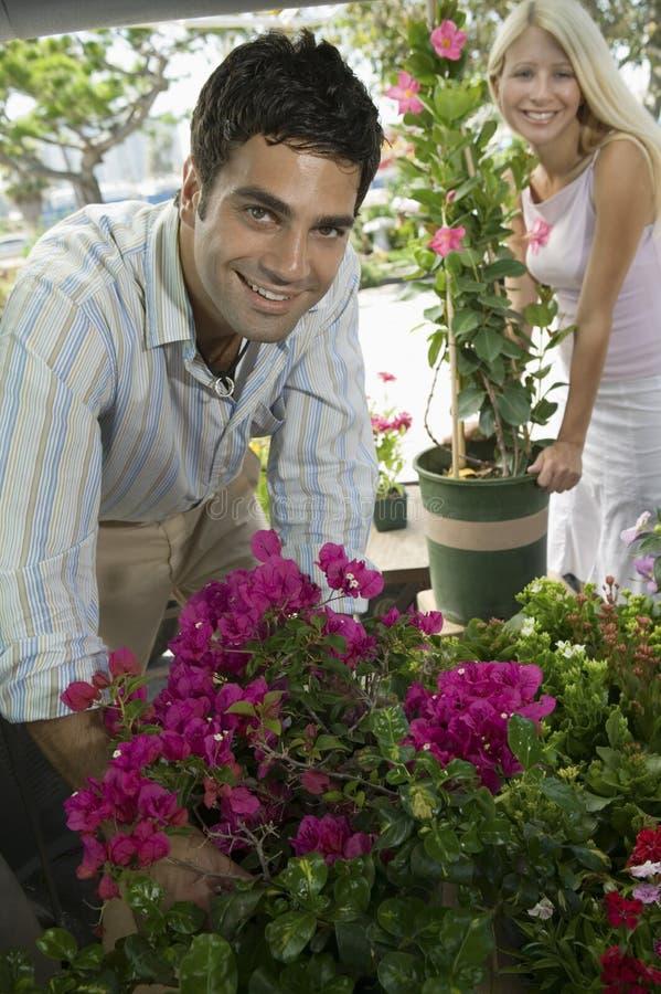 Couples choisissant des fleurs à la pépinière de centrale, image stock