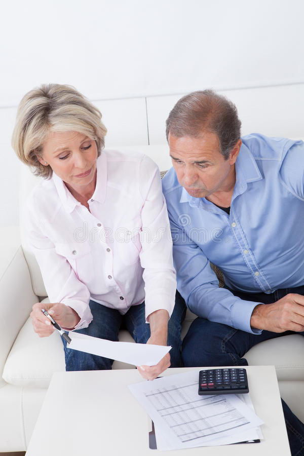 Couples choqués regardant la facture photographie stock