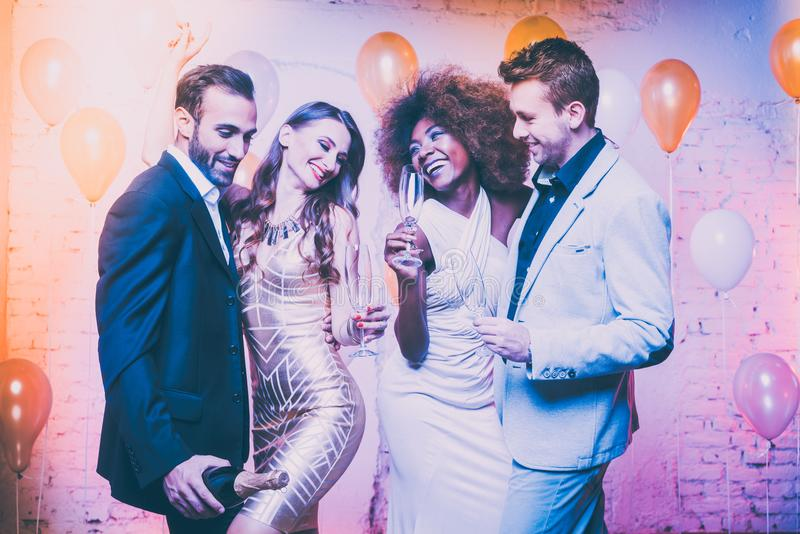 Couples in a club celebrating new years eve dancing into midnigh. T with sparkling wine stock photography
