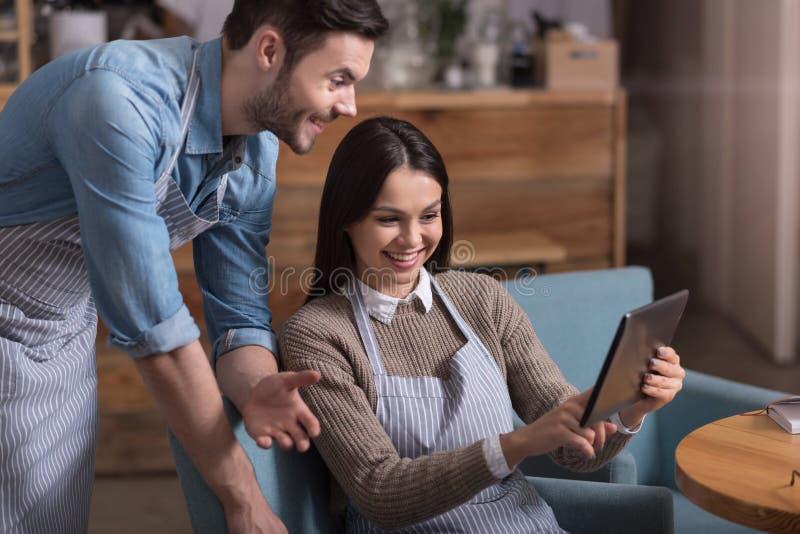 Couples comblés satisfaisants riant et à l'aide du comprimé photo stock