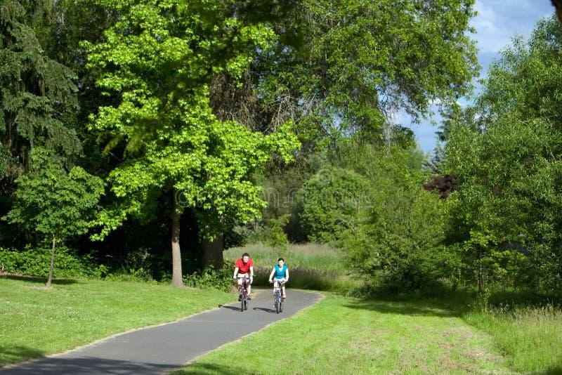 Couples conduisant un vélo - horizontal photographie stock libre de droits