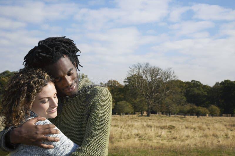 Couples contestés embrassant dans le domaine images stock