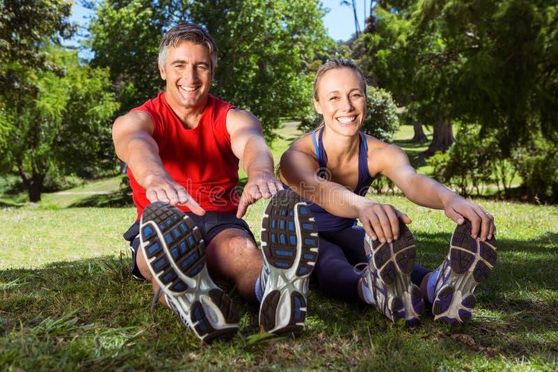 Couples convenables s'étendant en parc photographie stock libre de droits