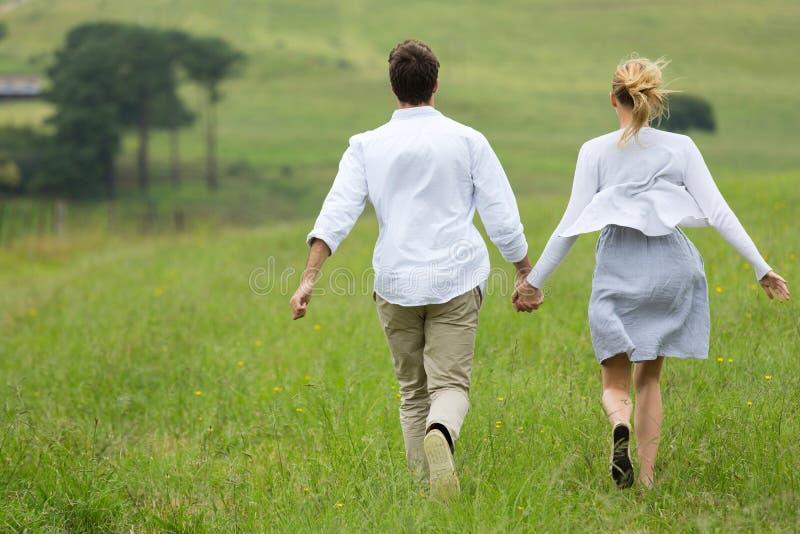 Couples courant le champ vert images libres de droits
