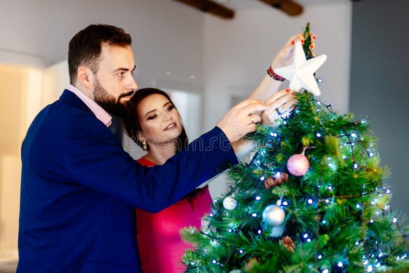 Couples décorant l'arbre de Noël photographie stock