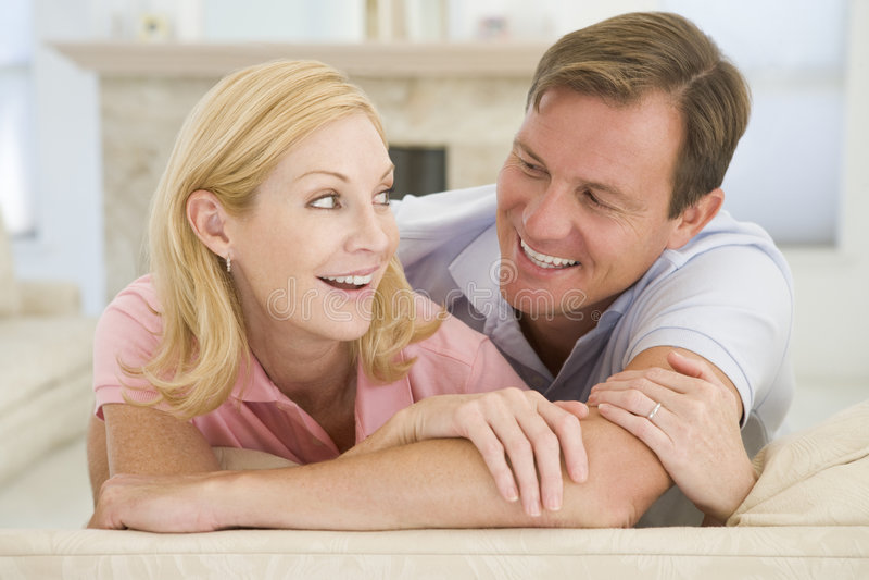 Couples détendant dans la salle de séjour et le sourire image libre de droits