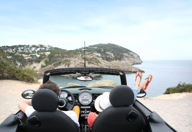 Couples détendant dans le cabriolet par la mer image libre de droits