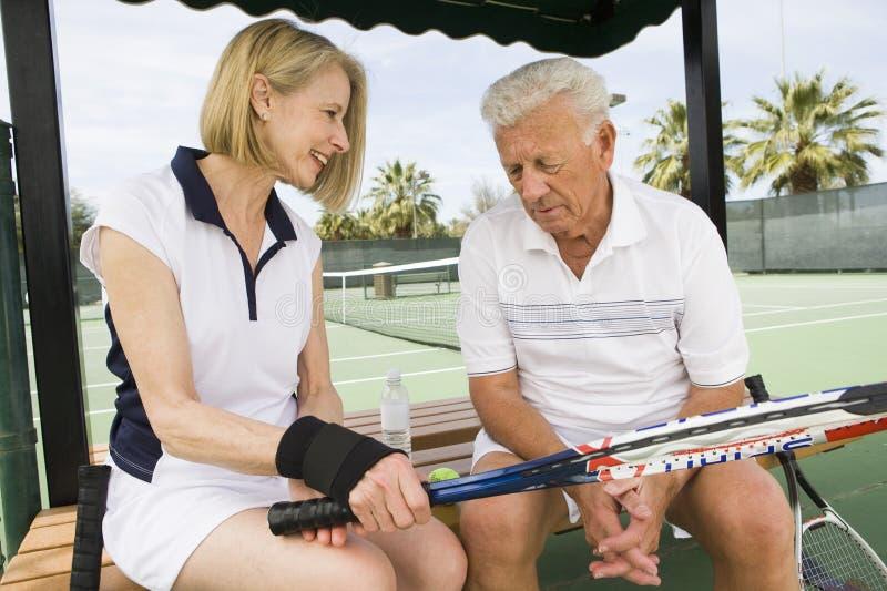 Couples détendant sur le banc après avoir joué le tennis image stock