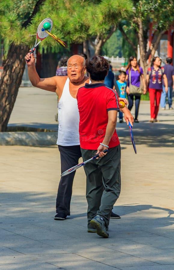 Couples d'aîné jouant le jeu chinois de Jianzi avec un exploit coloré images libres de droits