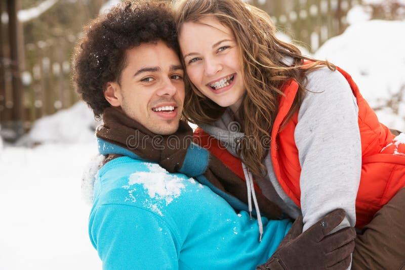 Couples d'adolescent romantiques ayant l'amusement dans la neige photo libre de droits