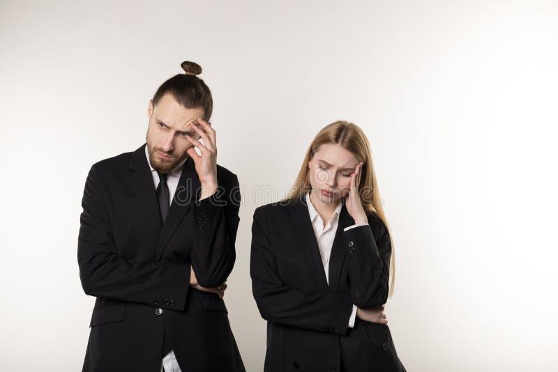 Couples d'affaires de renversement portant les costumes noirs au-dessus du fond blanc, fonctionnant ensemble images stock