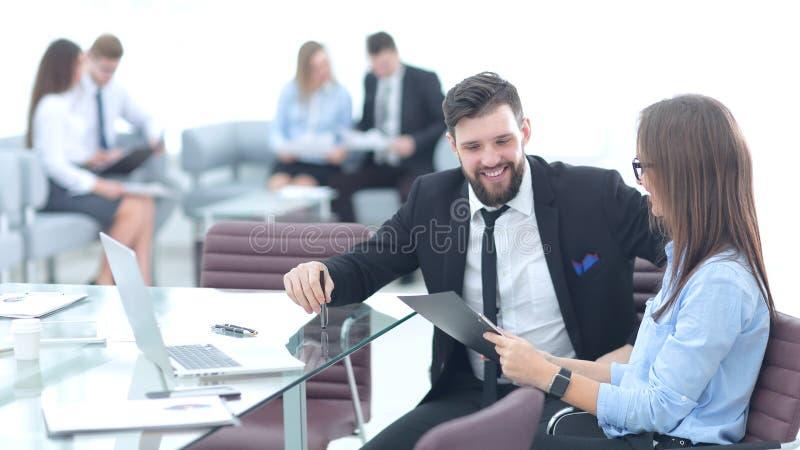 Couples d'affaires discutant la feuille de travail se reposant au bureau image stock