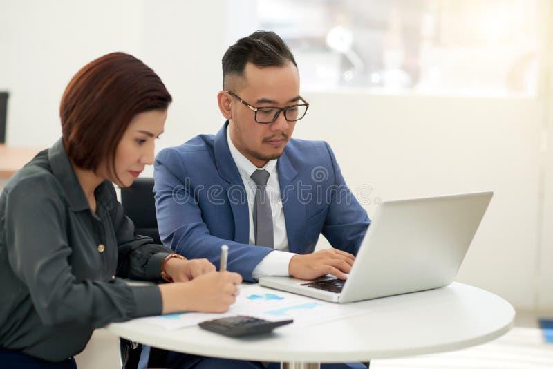 Couples d'affaires fonctionnant ensemble au bureau images libres de droits