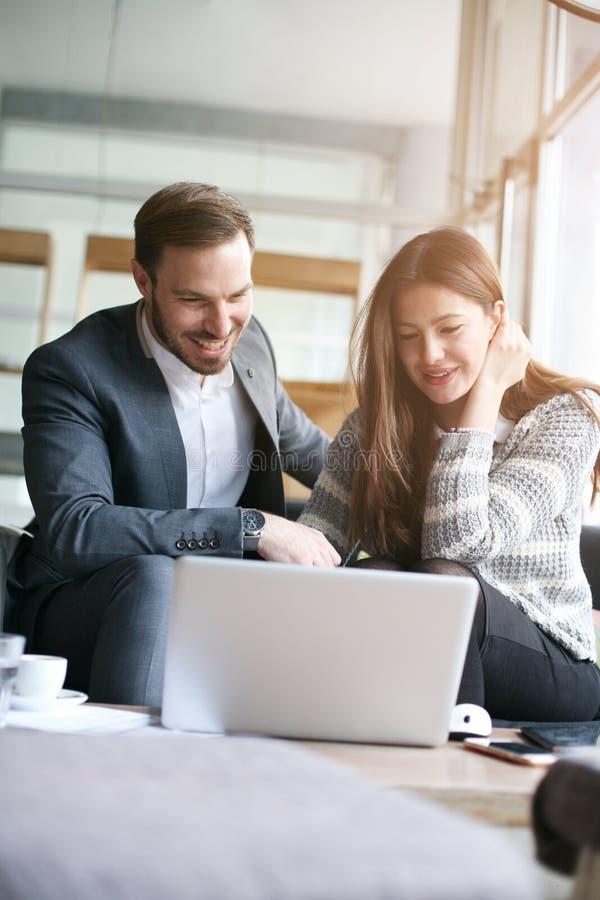 Couples d'affaires fonctionnant ensemble en café image stock