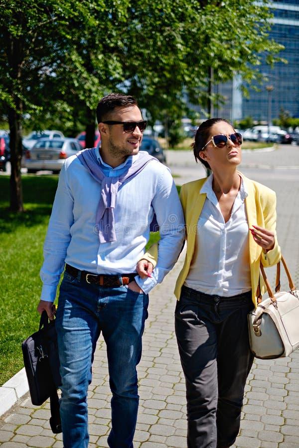 Couples d'affaires marchant sur le trottoir photographie stock libre de droits