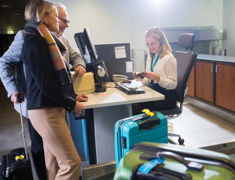 Couples d'affaires regardant le personnel vérifiant le passeport à l'aéroport ch images stock