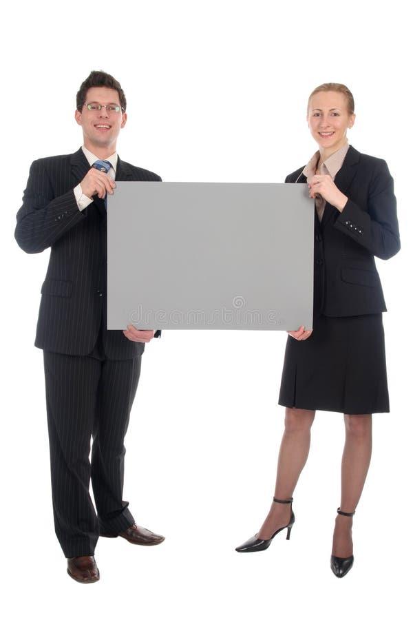 Couples d'affaires retenant le signe blanc images libres de droits