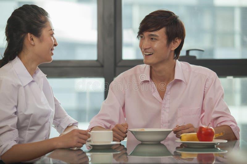 Couples d'affaires souriant et mangeant le petit déjeuner ensemble photographie stock