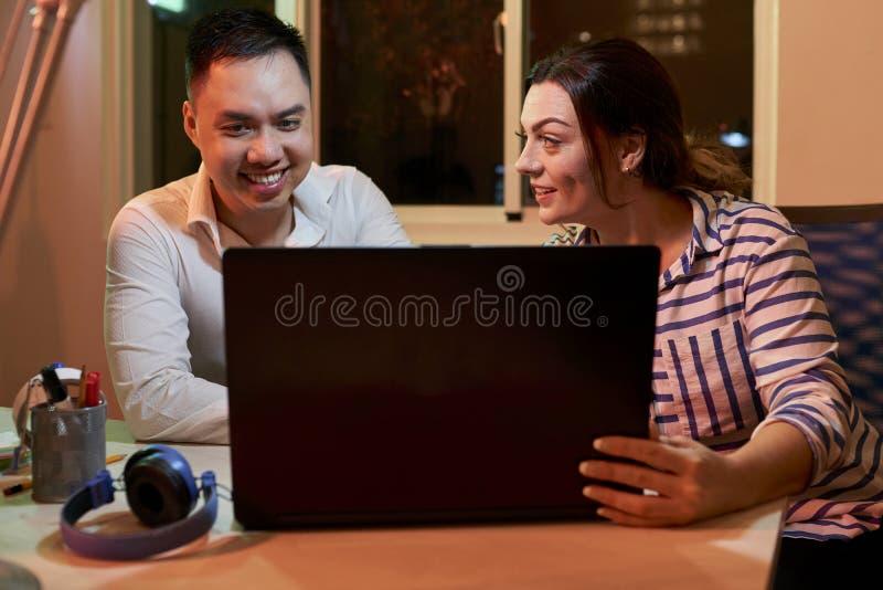 Couples d'affaires travaillant sur l'ordinateur portable au bureau image stock