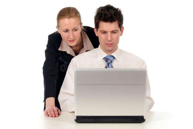Couples d'affaires travaillant sur l'ordinateur portatif photographie stock libre de droits