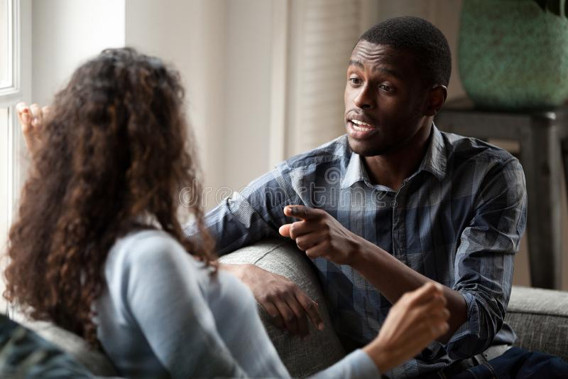 Couples d'africain noir discutant se reposer sur le divan à la maison photo stock