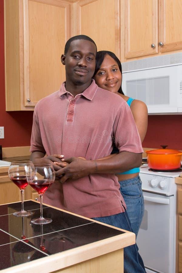 Couples d'Afro-américain étreignant dans la cuisine images stock