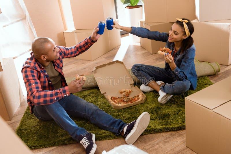 couples d'afro-américain mangeant de la pizza et tintant avec des boîtes de soude en nouvel appartement photo libre de droits