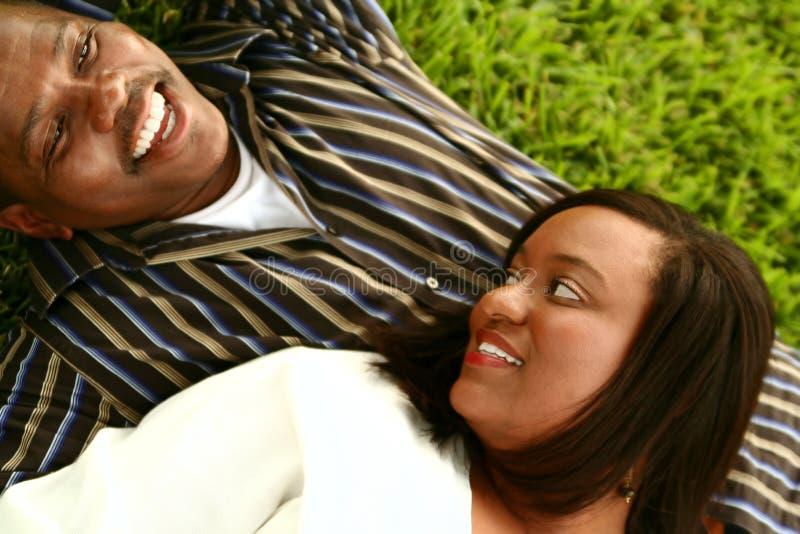 Couples d'Afro-américain s'étendant au sol photographie stock