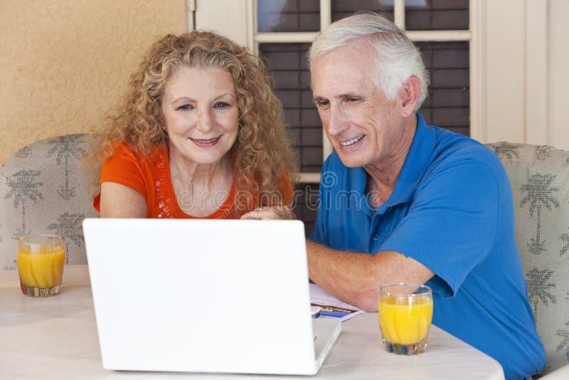 Couples d'homme aîné et de femme sur l'ordinateur portable images libres de droits