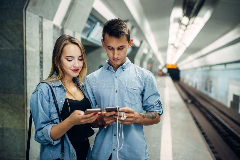 Couples d'intoxiqué de téléphone utilisant l'instrument dans le souterrain photos stock