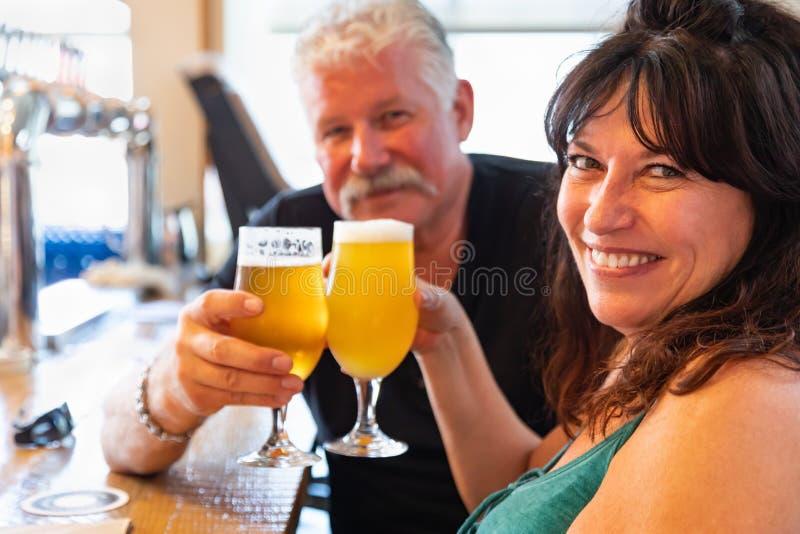 Couples d'une cinquantaine d'années attrayants grillant des verres d'abeille micro de brew photos stock