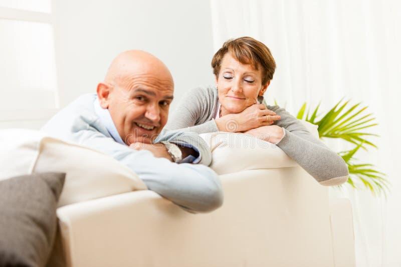 Couples d'une cinquantaine d'années décontractés se reposant sur un sofa images stock