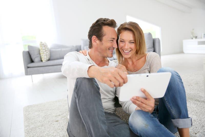 Couples d'une cinquantaine d'années ayant l'amusement utilisant le comprimé image stock