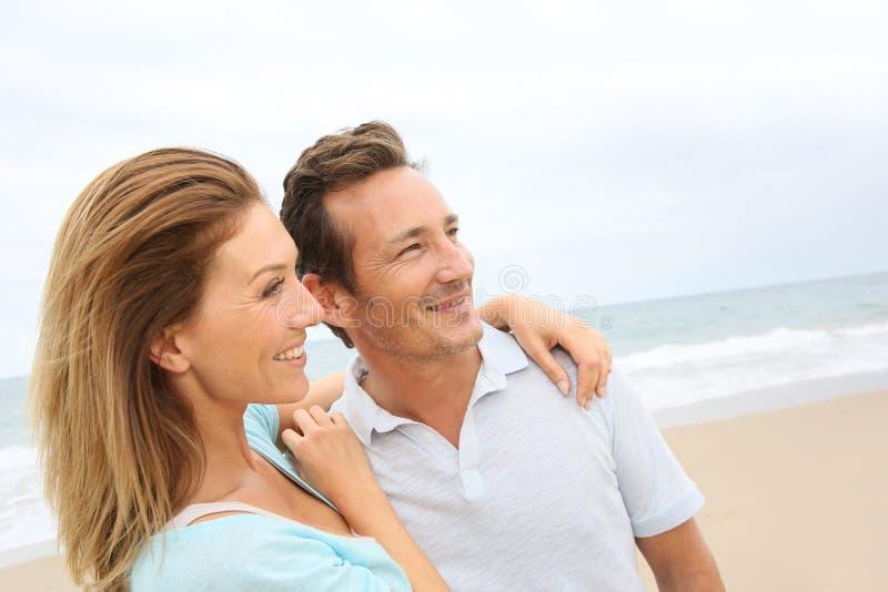 Couples d'une cinquantaine d'années heureux ayant l'amusement sur la plage photographie stock