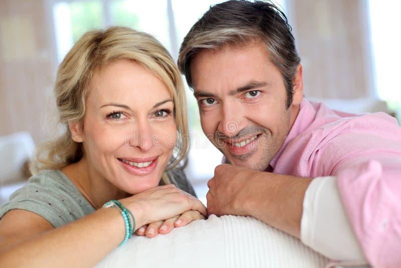 Couples d'une cinquantaine d'années heureux se penchant sur le sofa photographie stock libre de droits
