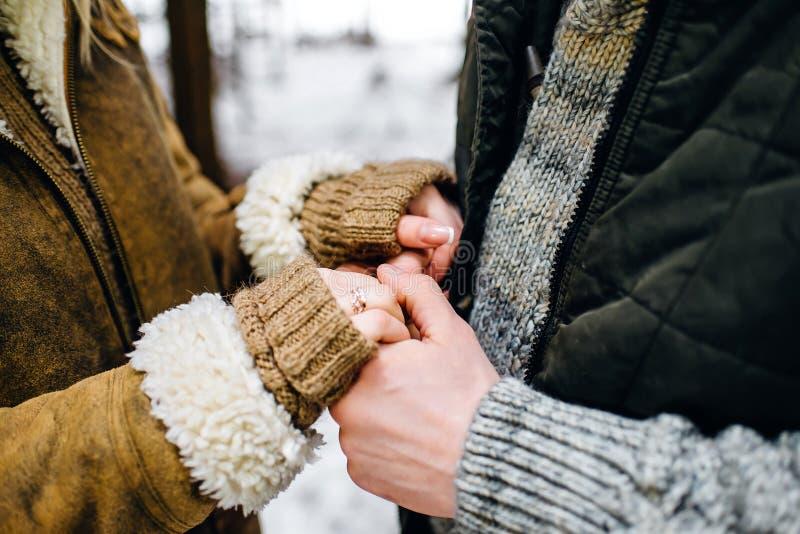 couples dans des chandails d'hiver et des manteaux chauds tenant des mains images libres de droits