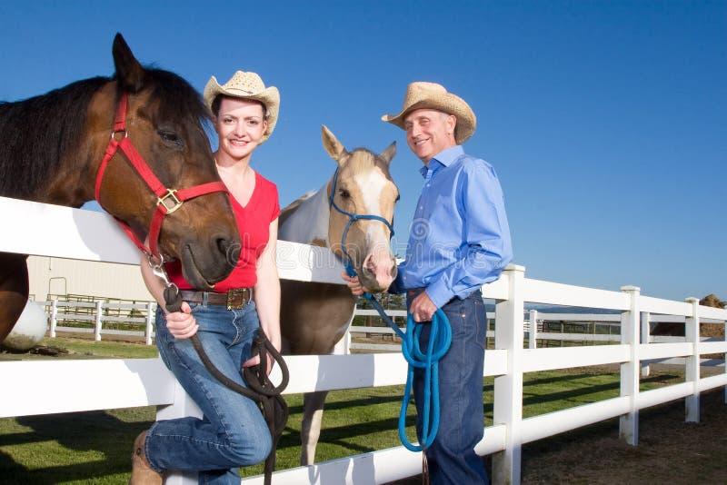 Couples dans des chapeaux de cowboy avec des chevaux - horizontaux photographie stock
