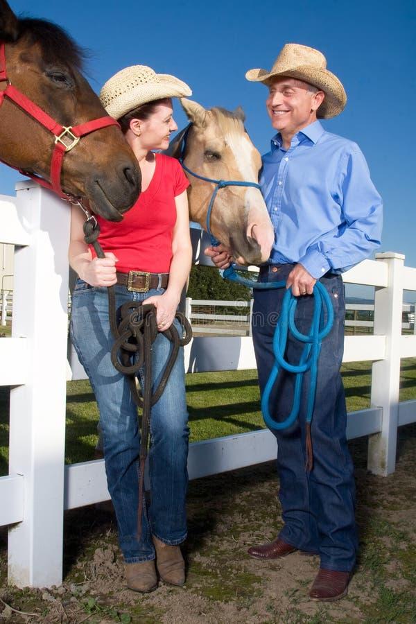Couples dans des chapeaux de cowboy avec des chevaux - verticale image libre de droits